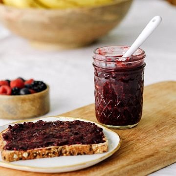 a glass jar filled with triple chia jam next to a slice of toast smeared with chia jam