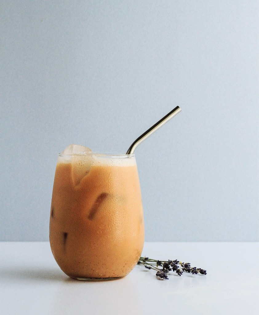head on view of lavender chai tea in a glass with straw.