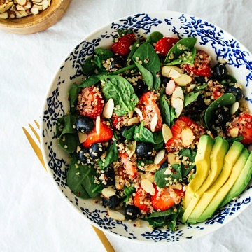 top down view of berry spinach quinoa salad and sliced avocado in a blue and white bowl with gold fork.