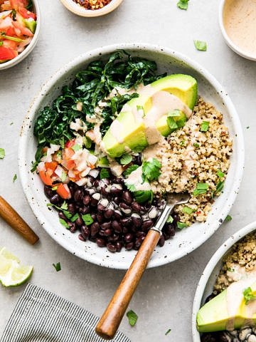 top down view black bean burrito bowl with wooden fork and items surrounding.