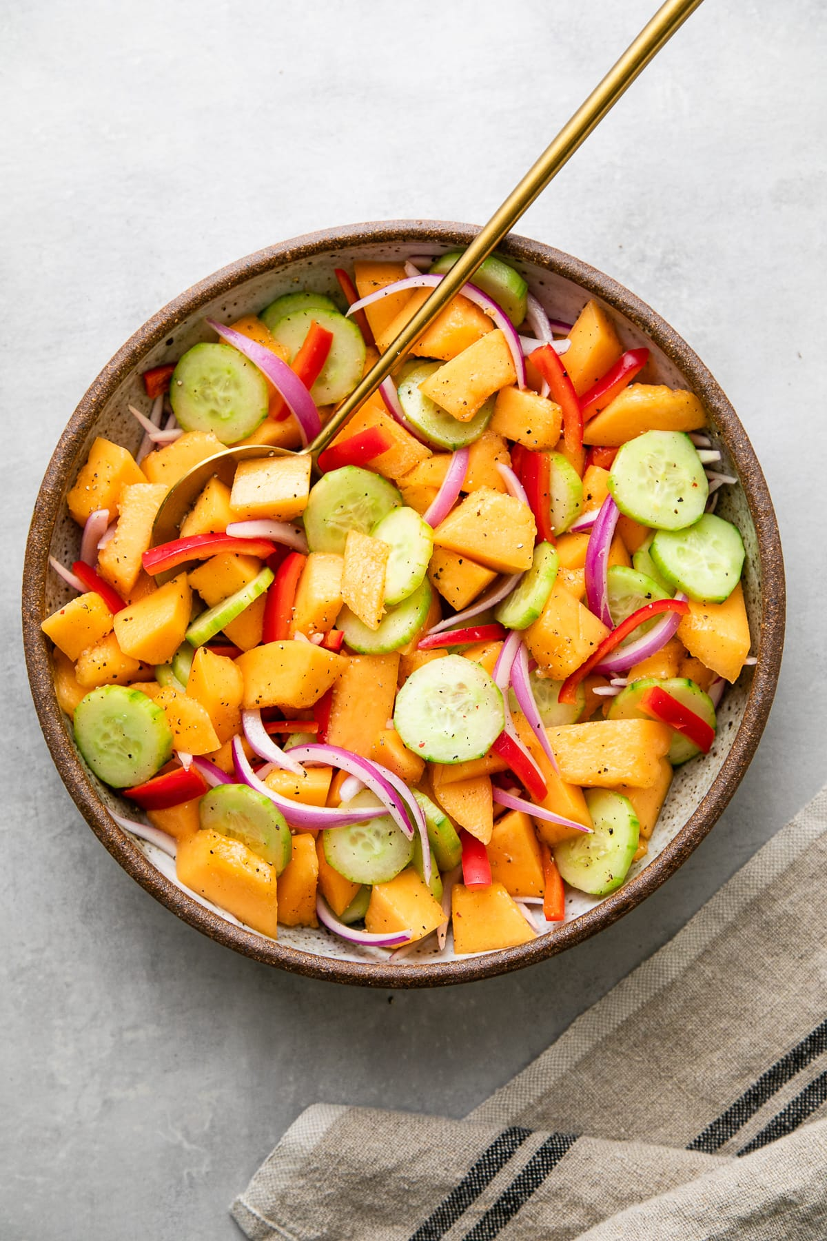 top down view of freshly mixed cantaloupe cucumber salad in a large bowl.