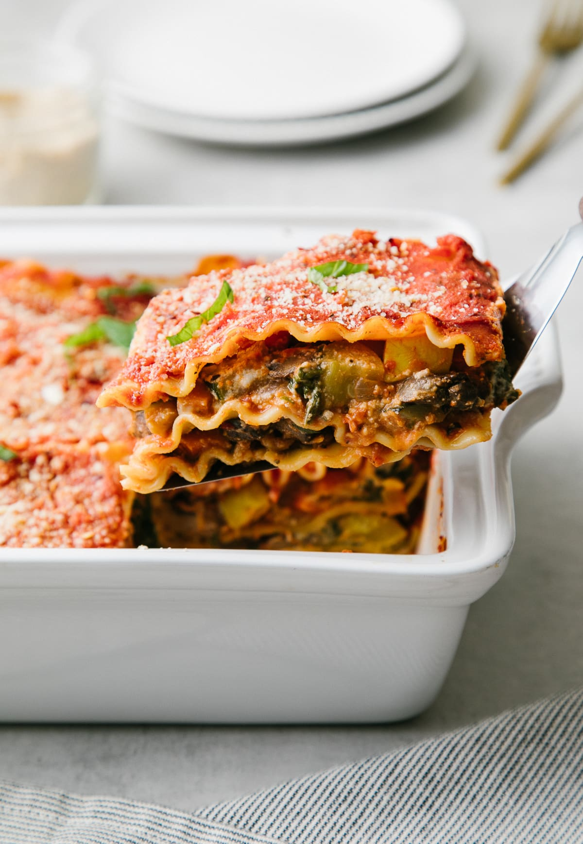 side angle view of sliced lasagna being taken from baking dish.