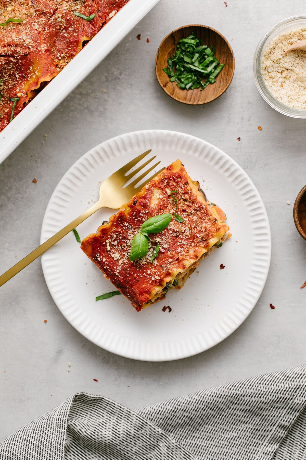 top down view of vegetable vegan lasagna on a white plate with fork and items surrounding.