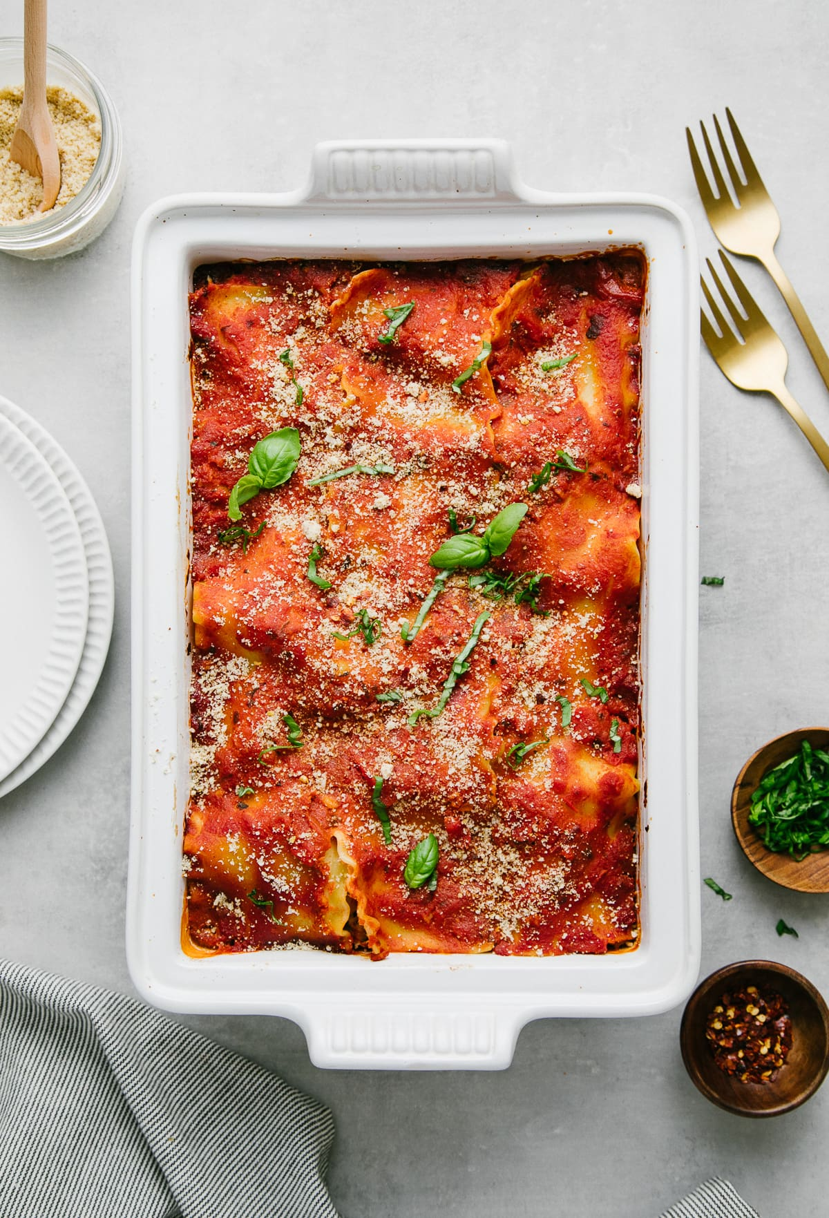 top down view of vegetable vegan lasagna topped with almond parmesan and fresh basil.