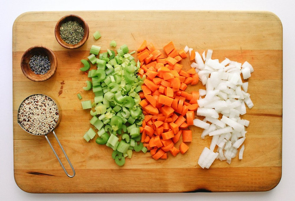 top down view of a cutting board with chopped celery, carrots, onion