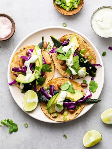 top down view of poblano tacos with crema on a plate.