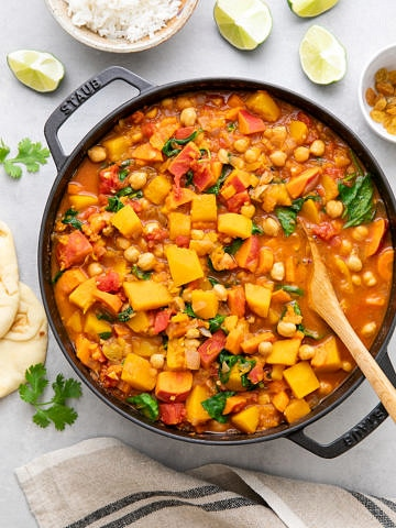 top down view of moroccan pumpkin and chickpea stew in a pot with items surrounding.