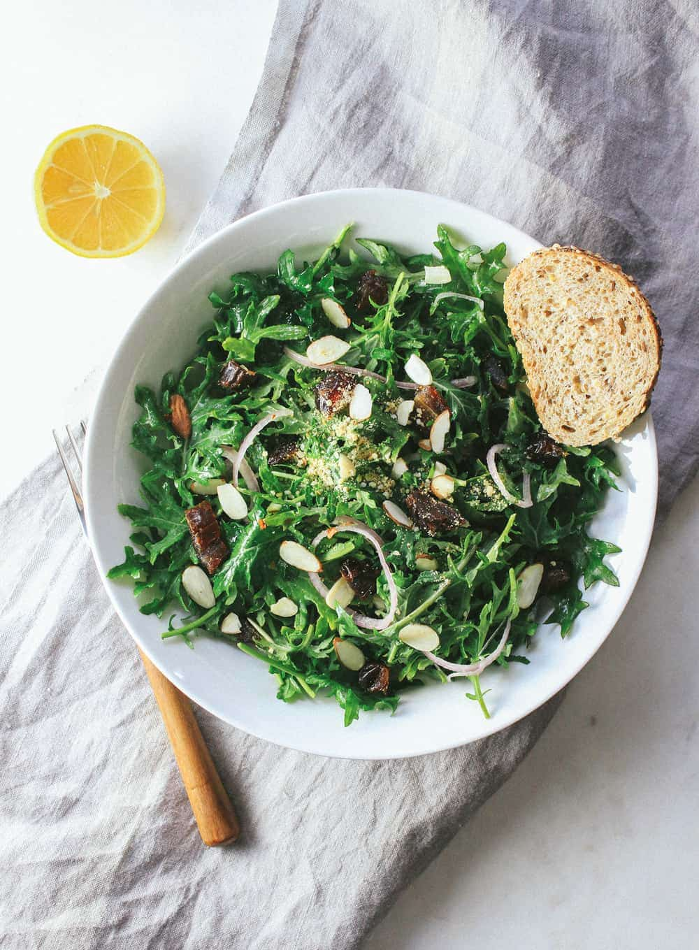 bowl full of kale, date and almond salad with wooden fork