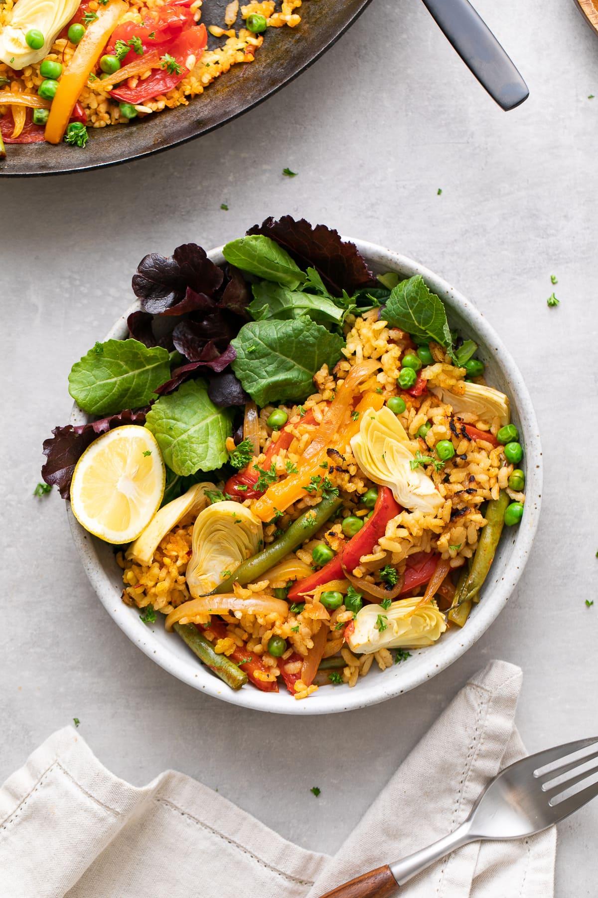 vista de arriba hacia abajo del tazón con verduras de hoja verde cubiertas con una porción de paella vegana vegetariana.