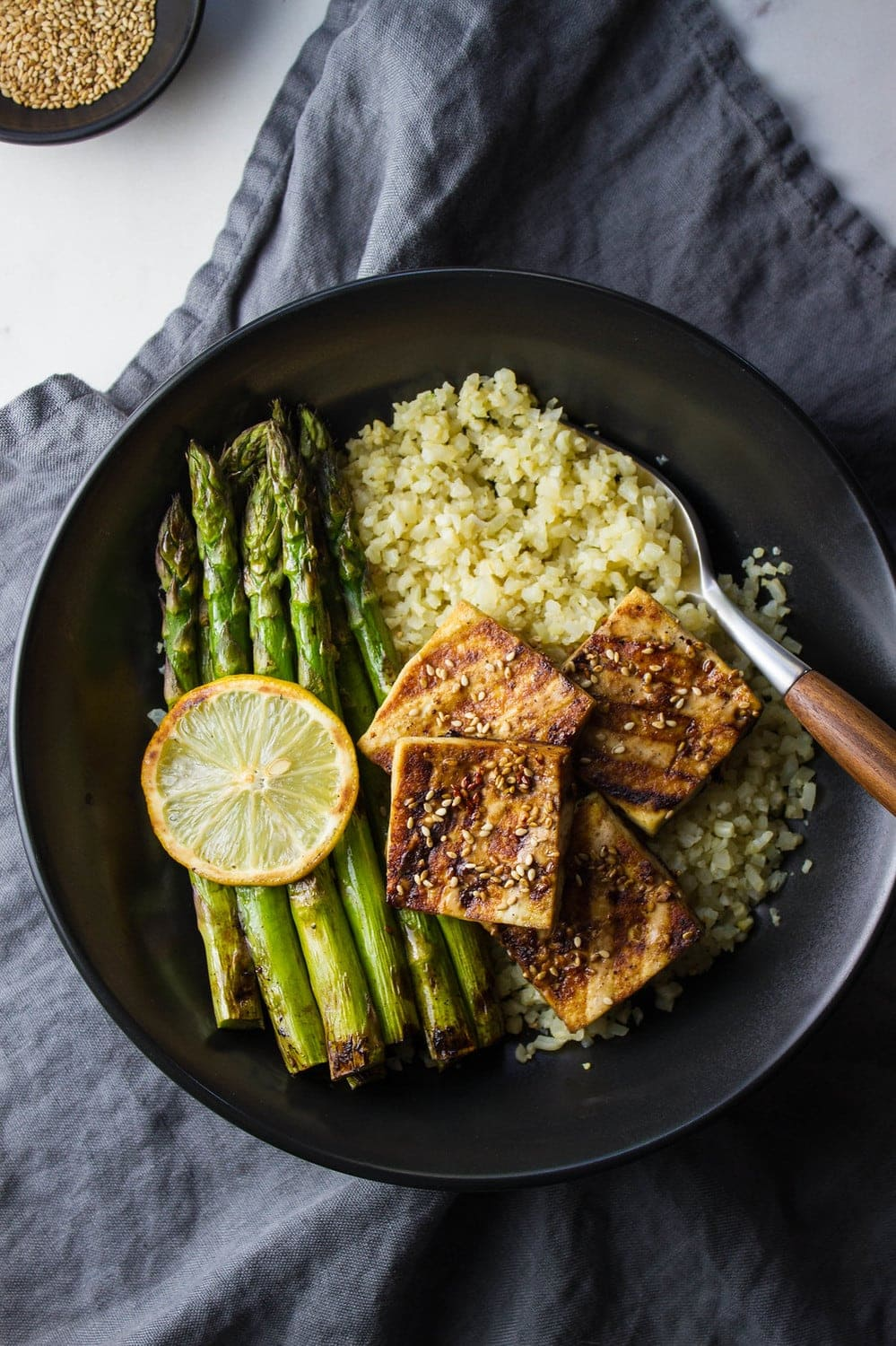top down view of a black plate with a serving of grilled tofu and asparagus with ginger cauliflower rice