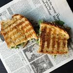 top down view of Grilled Hummus Sandwich + Sautéed Onion,Tomato & Arugula sliced in half