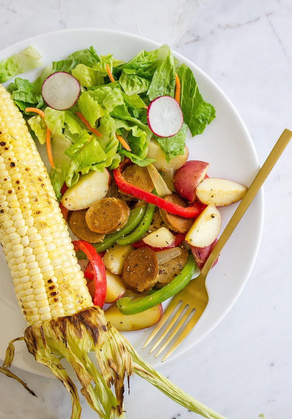 top down view of grilled corn, fresh garden salad and serving of sausage, peppers and potatoes on a white plate