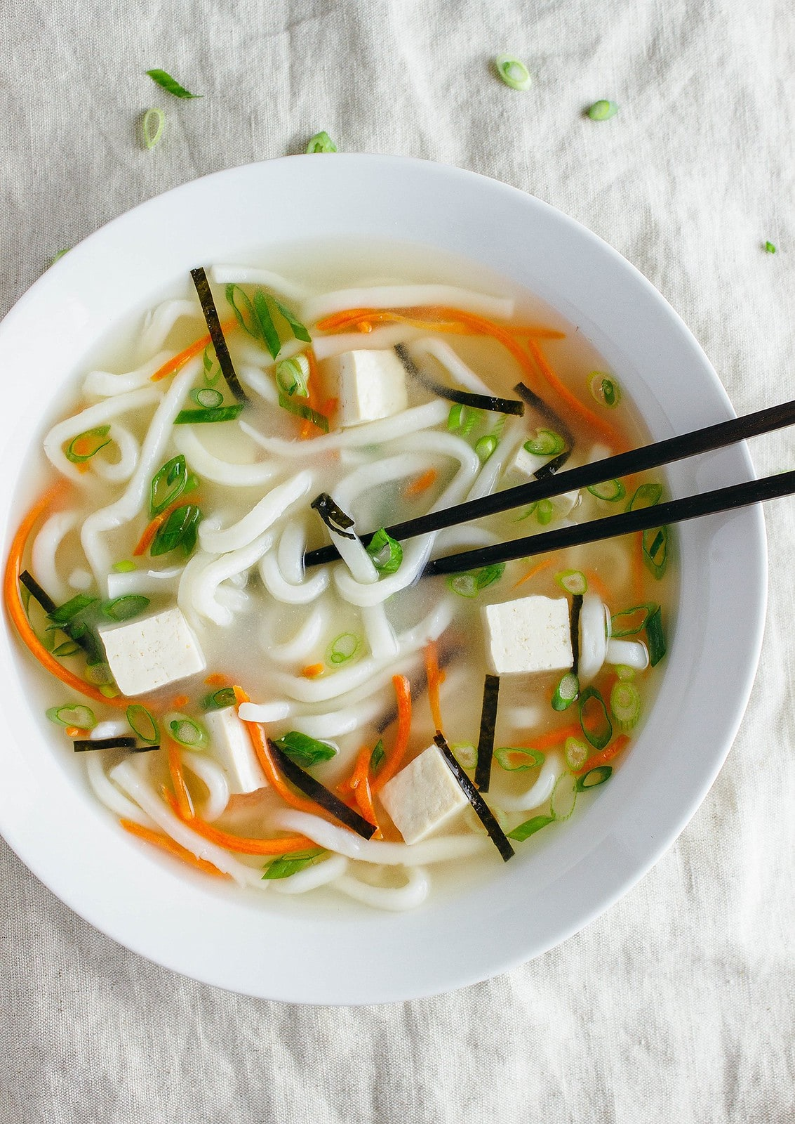 top down view of vegan miso noodle soup in a white bowl.