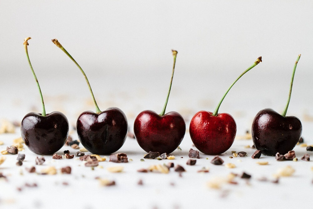 head on picture of 5 cherries lined up in a row with cacao nibs sprinkled all around.
