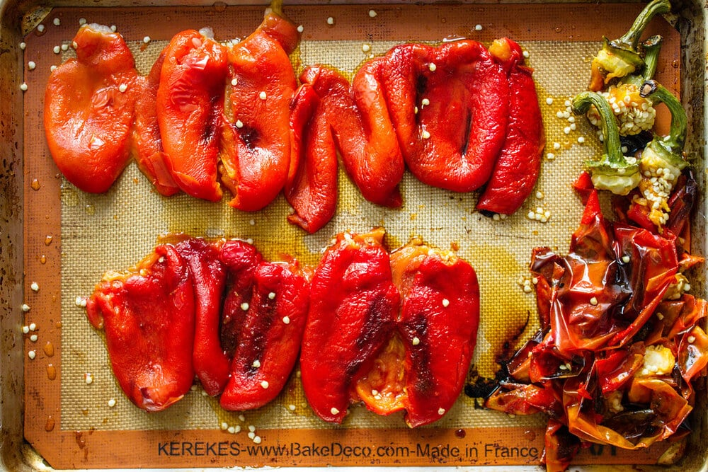 roasted red peppers steamed and peeled on a rimmed baking sheet.