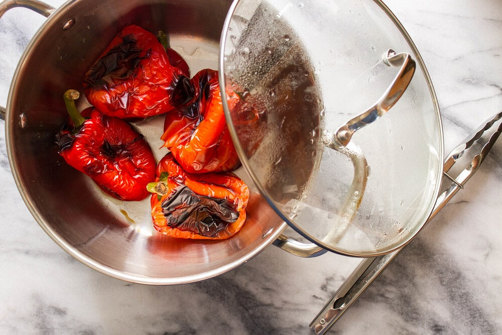 roasted bell peppers steaming in a large pot with lid.