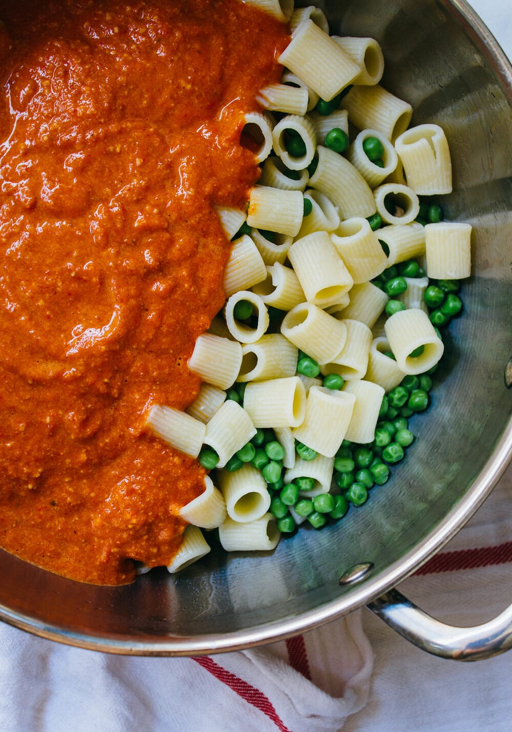 top down view of a pot with cooked pasta and peas, topped with romesco sauce before combining.