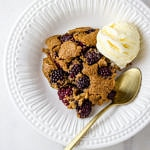 top down view of vegan blackberry cobbler in a white dish with gold spoon and scoop of vanilla ice cream.