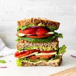 head on view of sliced and stacked mediterranean veggie sandwich with red peppers on a marble serving tray.