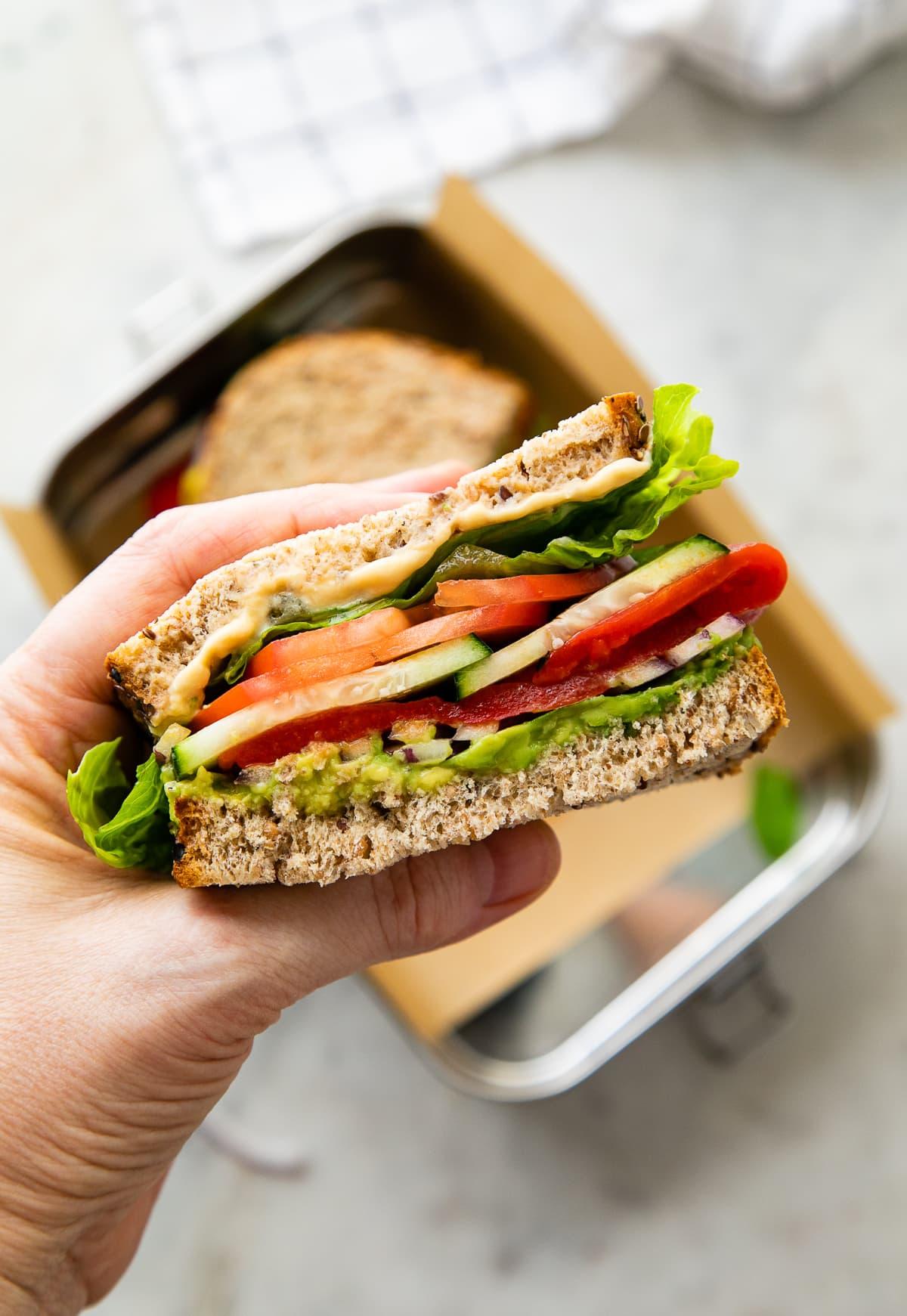 top down view of a hand holding a half of mediterranean veggie sandwich.
