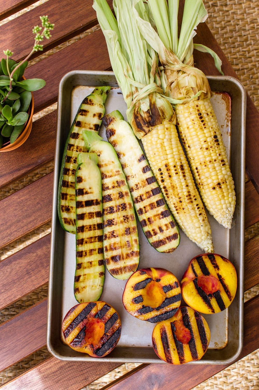 top down view of roasted zucchini, corn and peaches on a baking sheet.