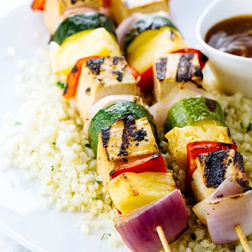 side angle view of grilled tofu skewers on a plate with cauliflower rice and pineapple teriyaki sauce.
