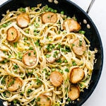 a top down view of skillet with alfredo noodles with king oyster mushrooms scallops and peas