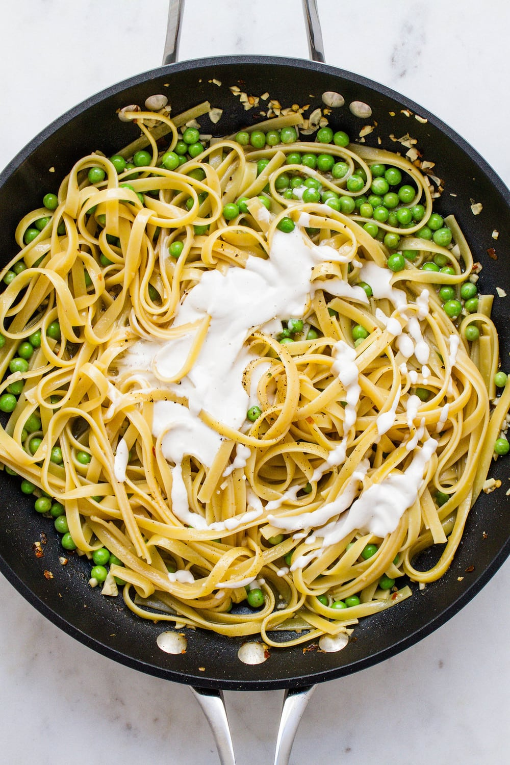 top down view of skillet with fettucine noodles, cashew alfredo sauce, and peas ready to be mixed