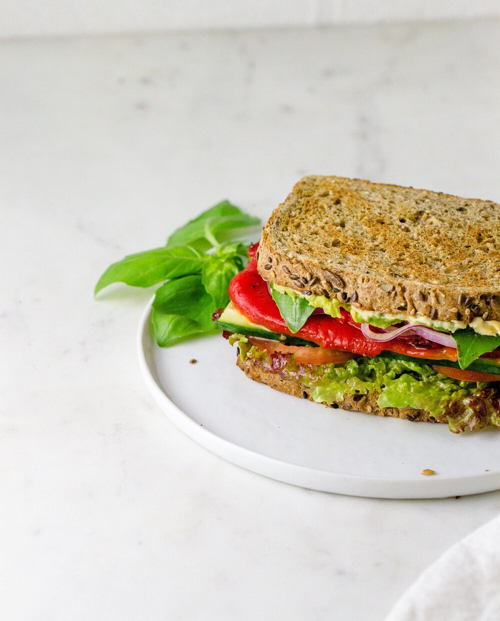 side angle view of roasted red pepper, hummus and avocado sandwich on a white plate.