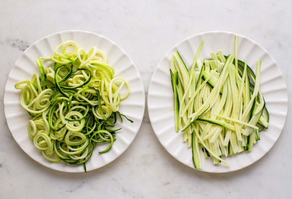 top down view of freshly sprialized and julienned zucchini noodles on a white plate.