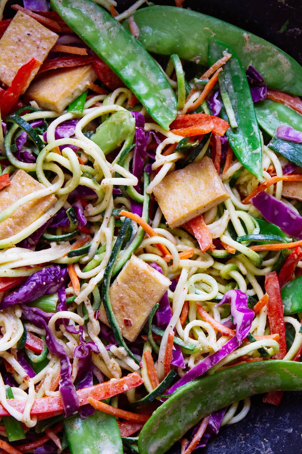 top down, up close, view of thai zucchini noodles with crispy tofu.