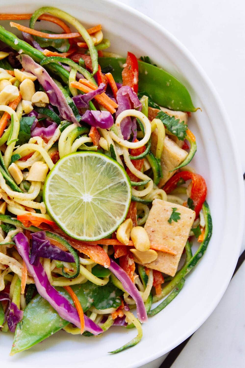 a white bowl filled with a serving of thai zucchini noodles and crispy tofu.