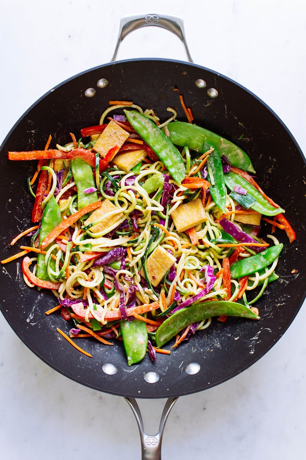 top down view of cooked thai zucchini noodle with crispy tofu in a wok.
