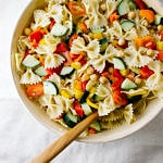 top down view of chickpea and vegetable pasta salad in a large serving bowl with wooden spoon.
