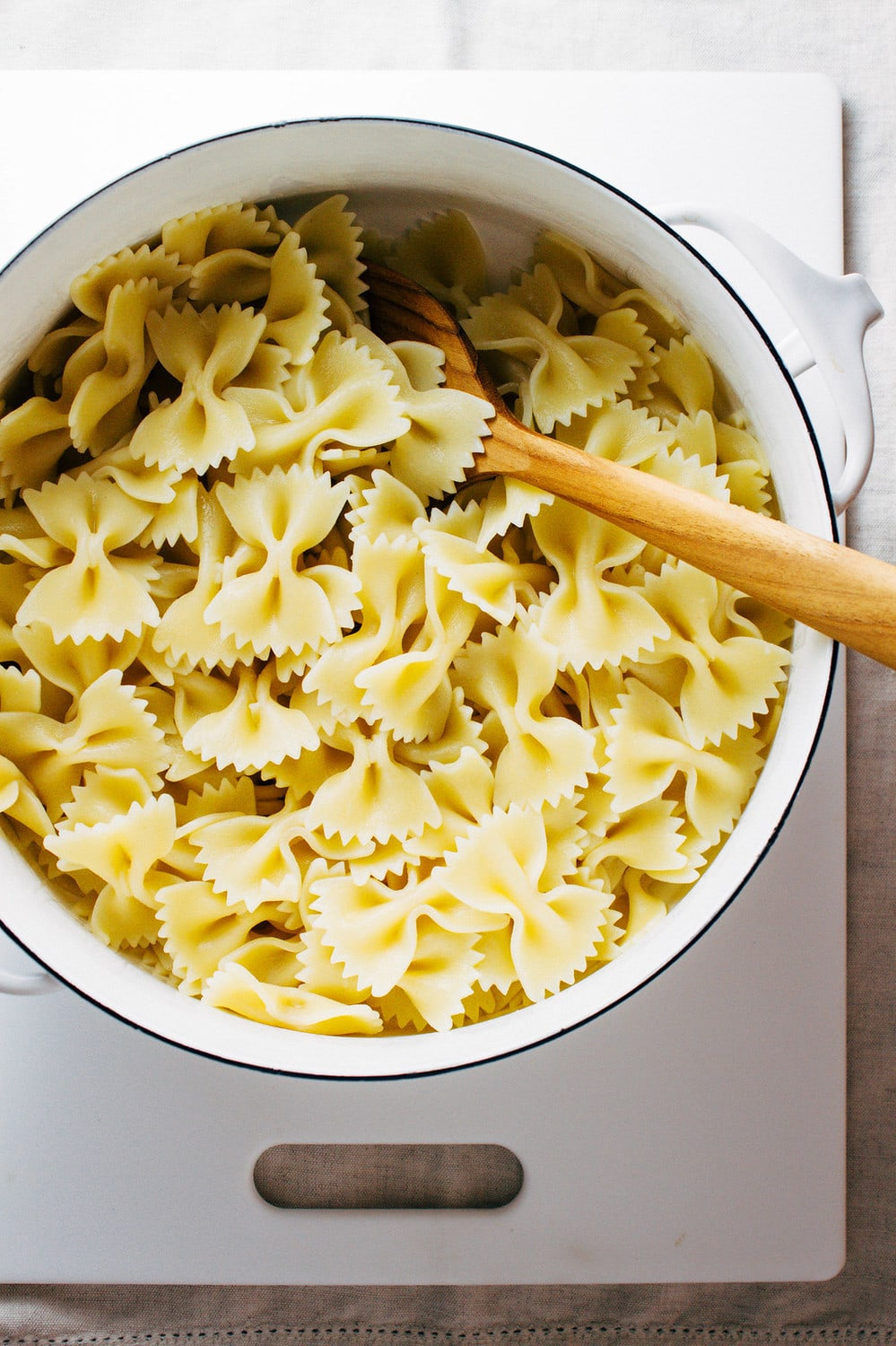 top down view of bow tie pasta cooked, rinsed and drained in a white pot with wooden spoon.