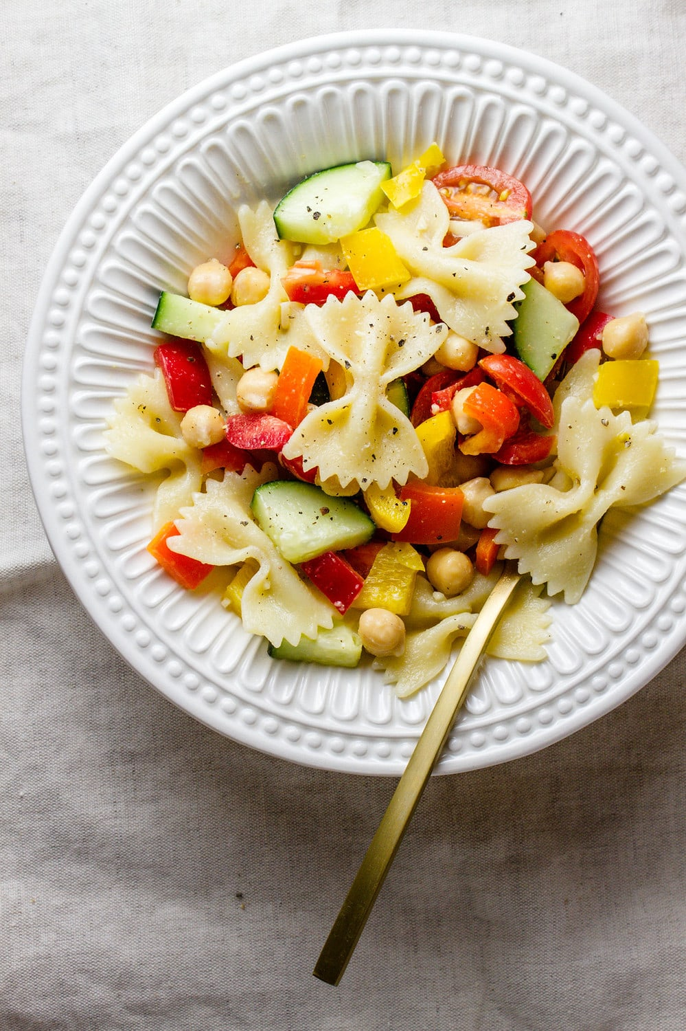top down view of a serving of chickpea vegetable pasta salad in a white bowl with gold fork.