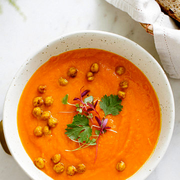 top down view of carrot sweet potato coriander soup with turmeric roasted chickpeas in a bowl.