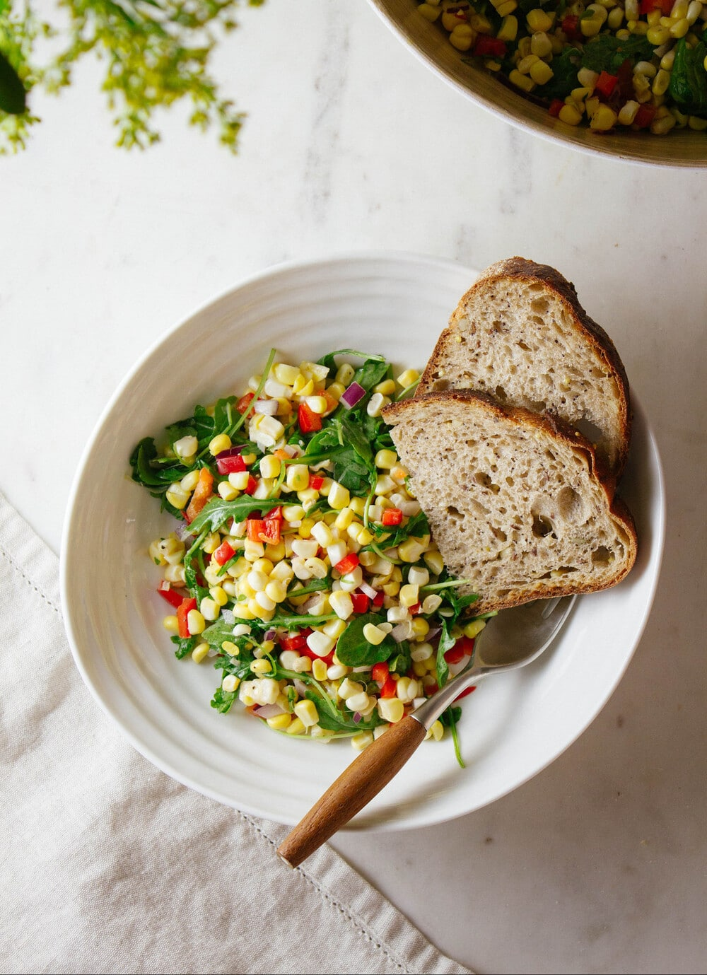 top down view of a serving of corn and arugula salad in a white bowl with sliced bread.