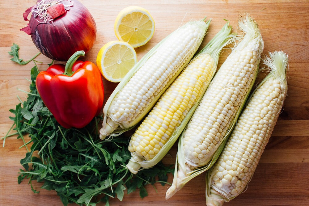 top down view of ingredients needed for corn and arugula salad on a wooden cutting board.