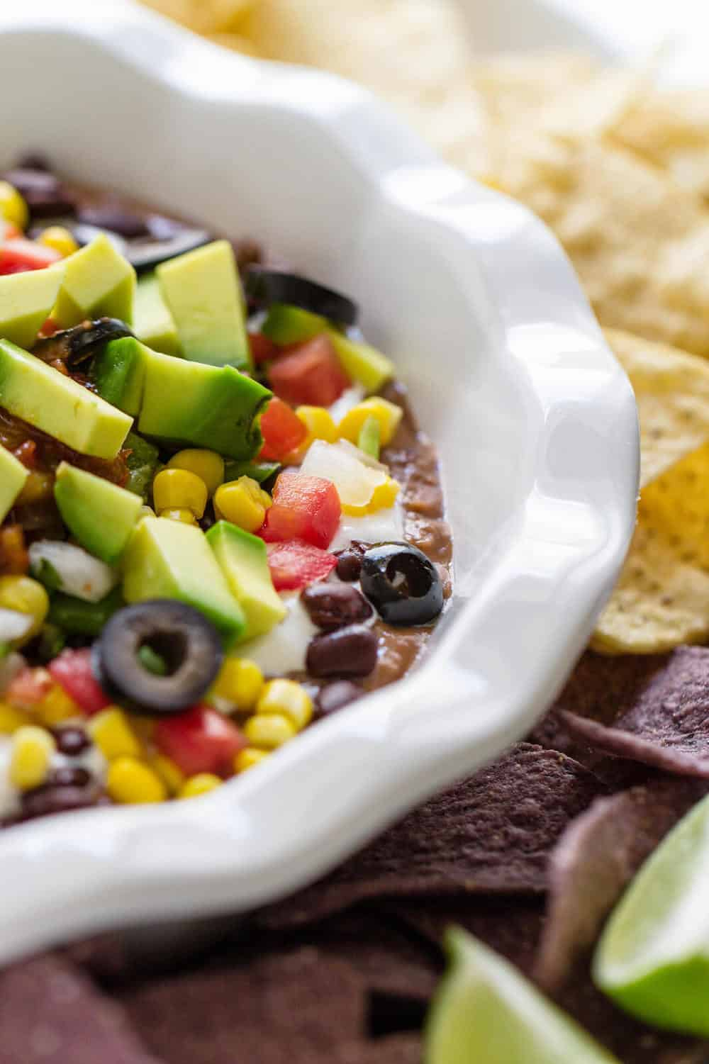 7 layer mexican bean dip in a white bowl with chips