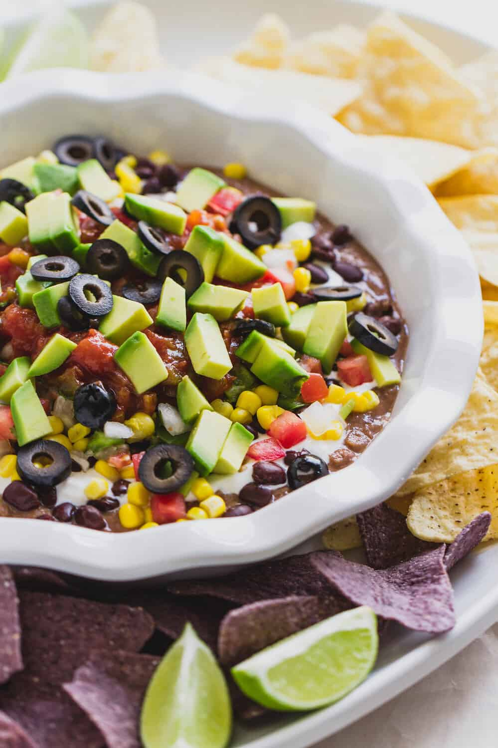 side angle view of vegan 7 layer dip with chips on a white plater.