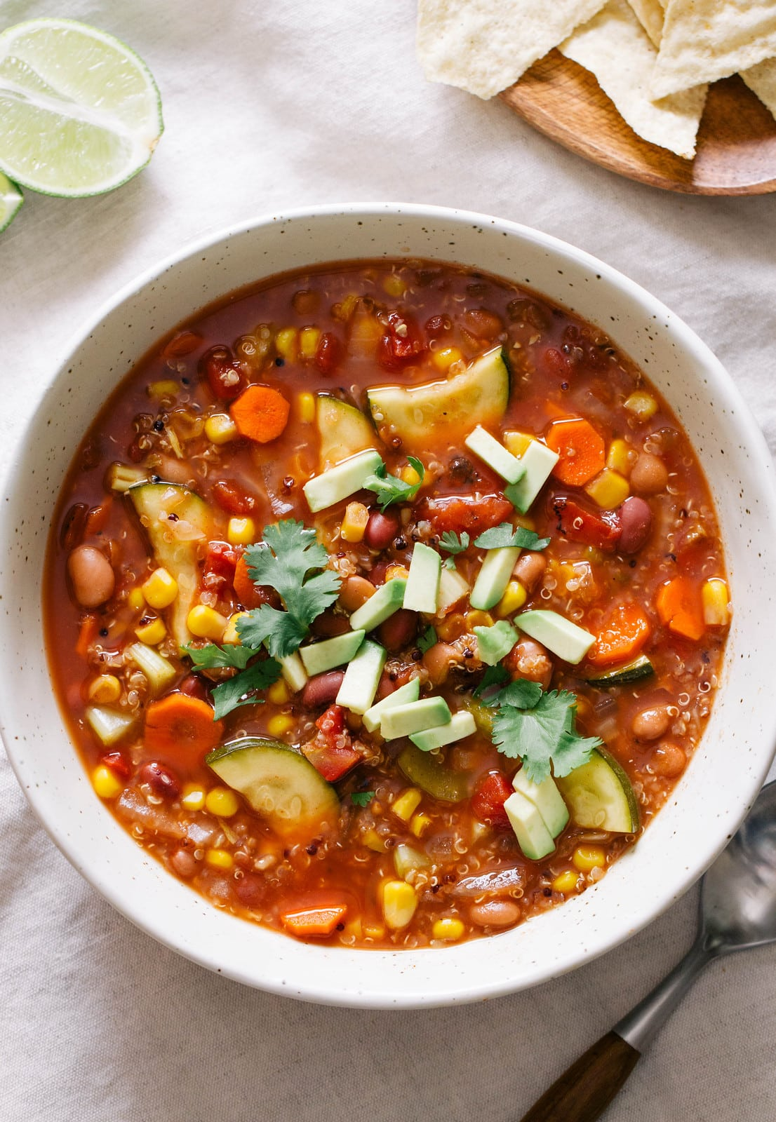 top down view of soup full of tex mex quinoa vegetable soup with items surrounding.