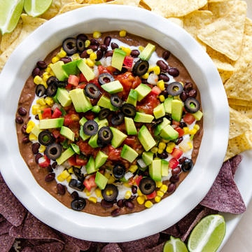 top down view of vegan 7 layer mexican bean dip in a white dish surrounded by tortilla chips.