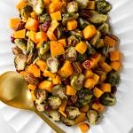 Roasted Brussels Sprouts + Squash w/ Cranberries & Pecans on a white serving platter