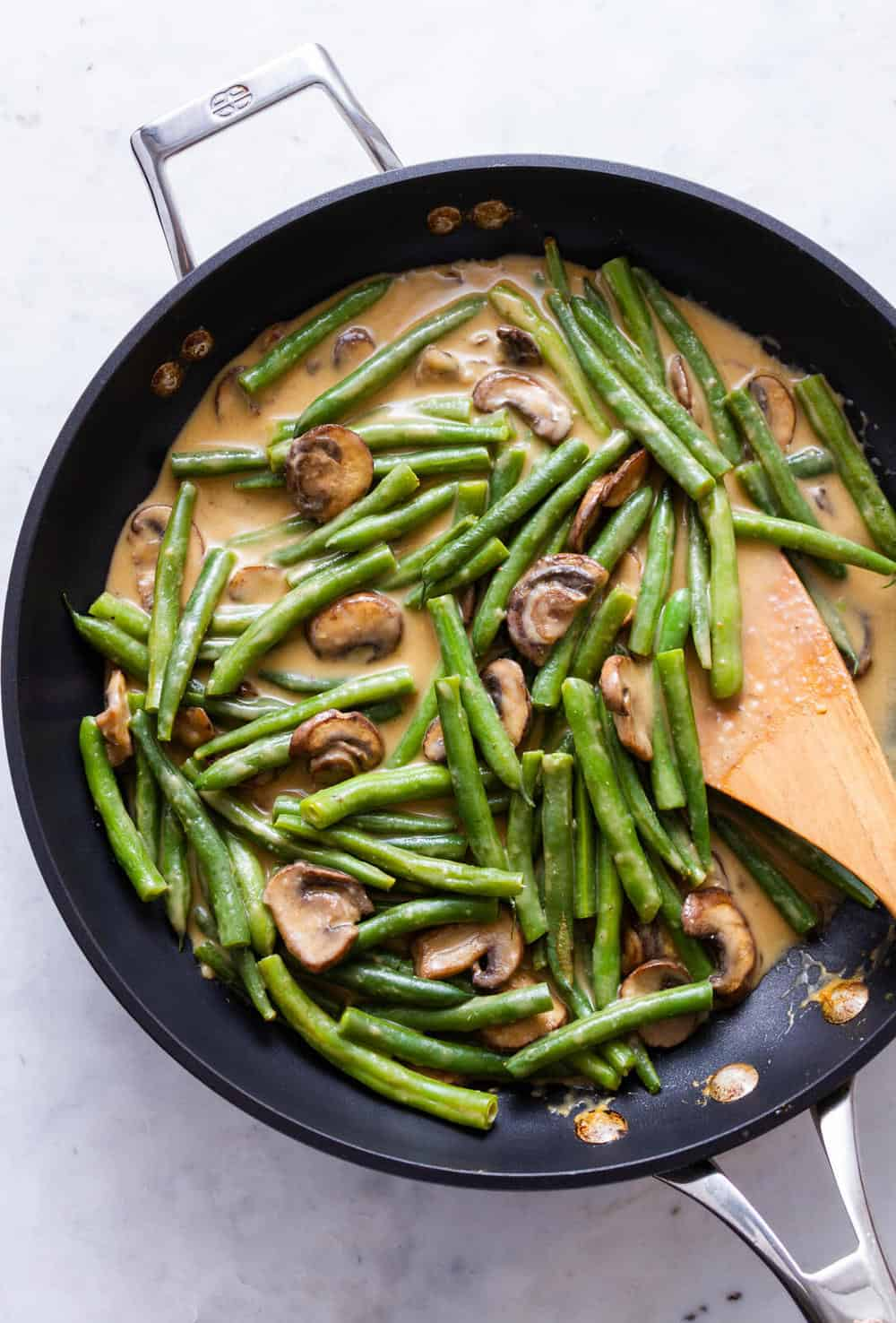 green bean casserole in the making, mixing the green beans with the mushroom gravy in a flat bottom, shallow pan