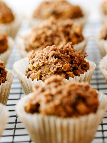 head on view of vegan pumpkin oat muffins cooling on a wire rack.