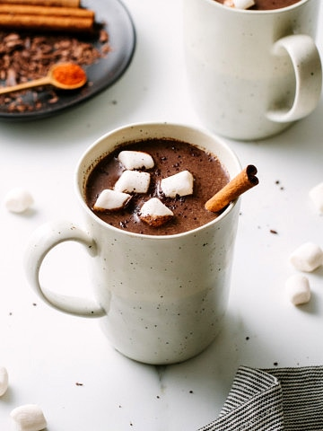 side angle view of Mexican hot chocolate in a mug with items surrounded.