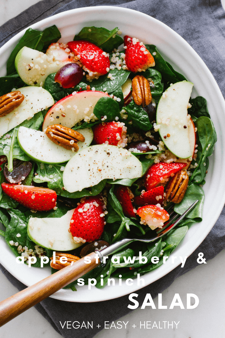 apple strawberry spinach quinoa salad in a white bowl with a fork
