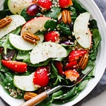 top down view of a spinach salad with strawberries, apples and quinoa in a serving bowl.