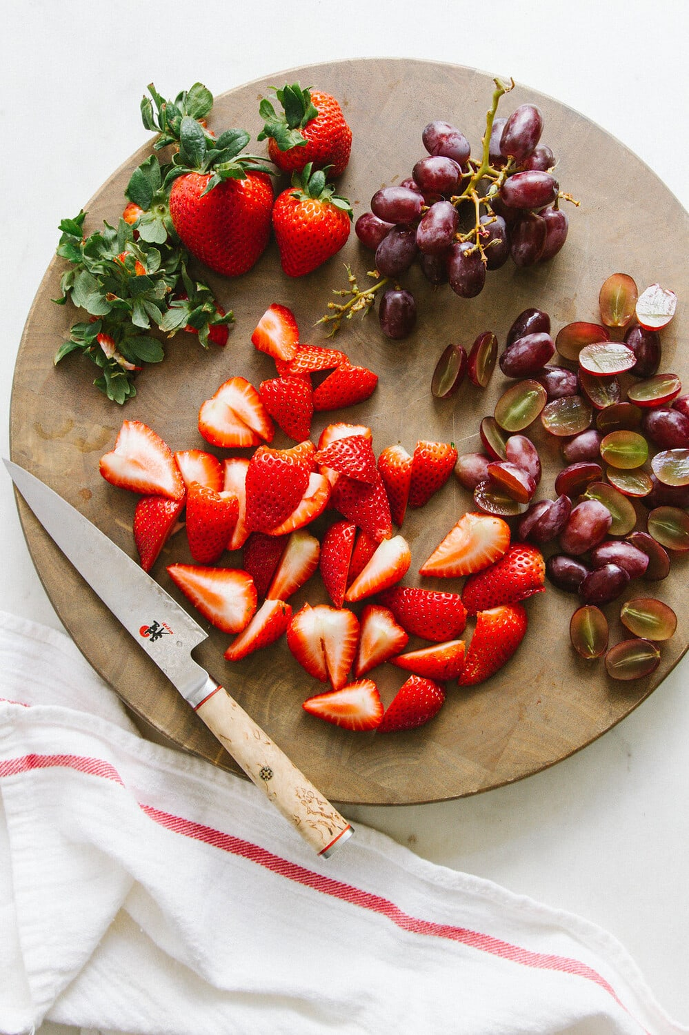 top down view of sliced strawberries and grapes on a circular wooden cutting board.